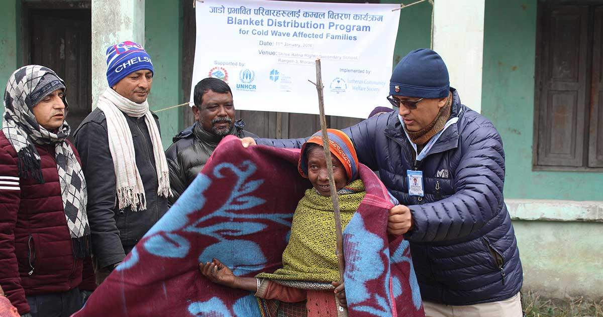 Mr Rajendra Kumar Raut (first from right) drapes a blanket around an elderly woman from Rangeli Municipality, Morang while Mr Joseph Soren, Chair of LCWS (second from right) looks on.
